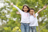 Two kids outdoor raise their hand and smile — Stock Photo