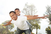Father giving his son piggyback ride outdoors — Stock Photo