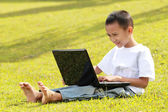 Happy little boy playing laptop on grass — Stock Photo