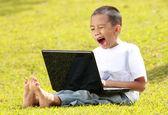 Little boy yawning when playing laptop — Stock Photo