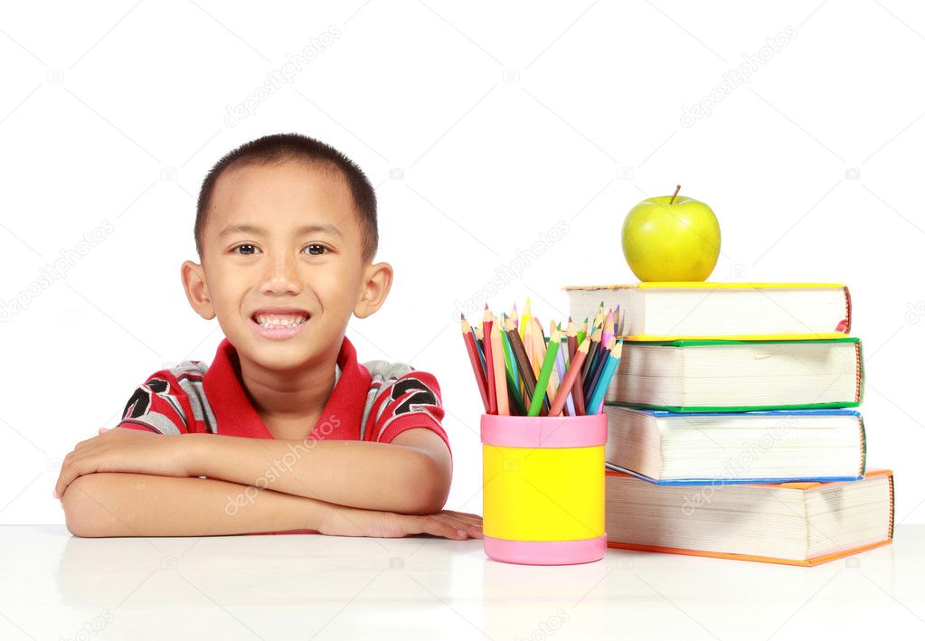 Smiling little boy with books on the table  Stock Photo #10637030