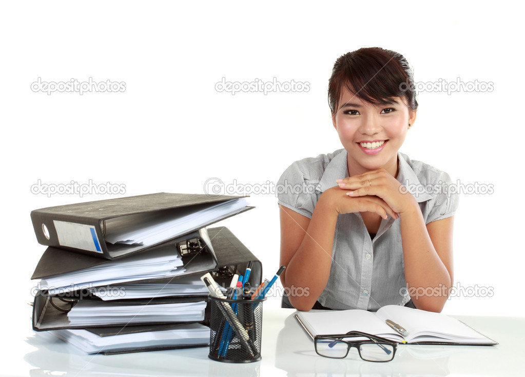 Young smiling business woman working on her paperwork. isolated over white background  Stock Photo #10638012