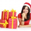 Girl in santa hat with pile of xmas gifts — Stock Photo