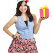 Teen girl in Santa hat presenting gift — Stock Photo #10670851