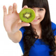 Pretty young woman holds kiwi in front of her eyes — Stock Photo