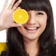 Woman holding lemons up to eyes and smiling. — Stock Photo