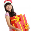 Woman in Santa hat holding Christmas gifts — Stock Photo