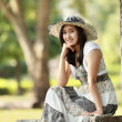 Young smiling asian woman sitting outdoor — Stock Photo