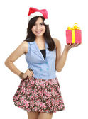 Teen girl in Santa hat presenting gift — Stock Photo