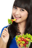 Portrait of smart young lady holding bowl of vegetable salad — Stock Photo