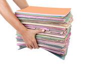 该名男子手持文件夹桩与旧文档和法案的堆栈 — 图库照片