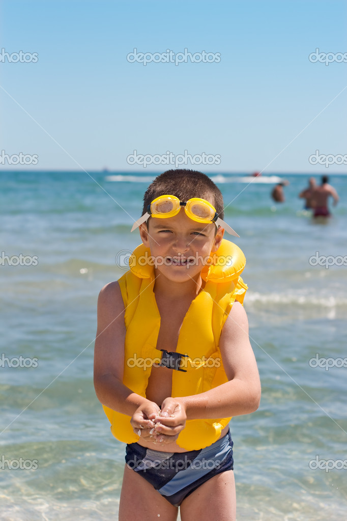 Boy with yellow safety equipment at the seaside — Stock Photo #10423985