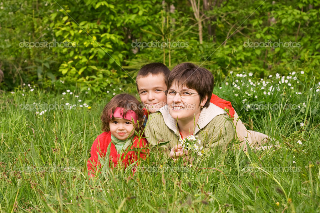 Woman and her kids laying in the spring grass — Stock Photo #10424021