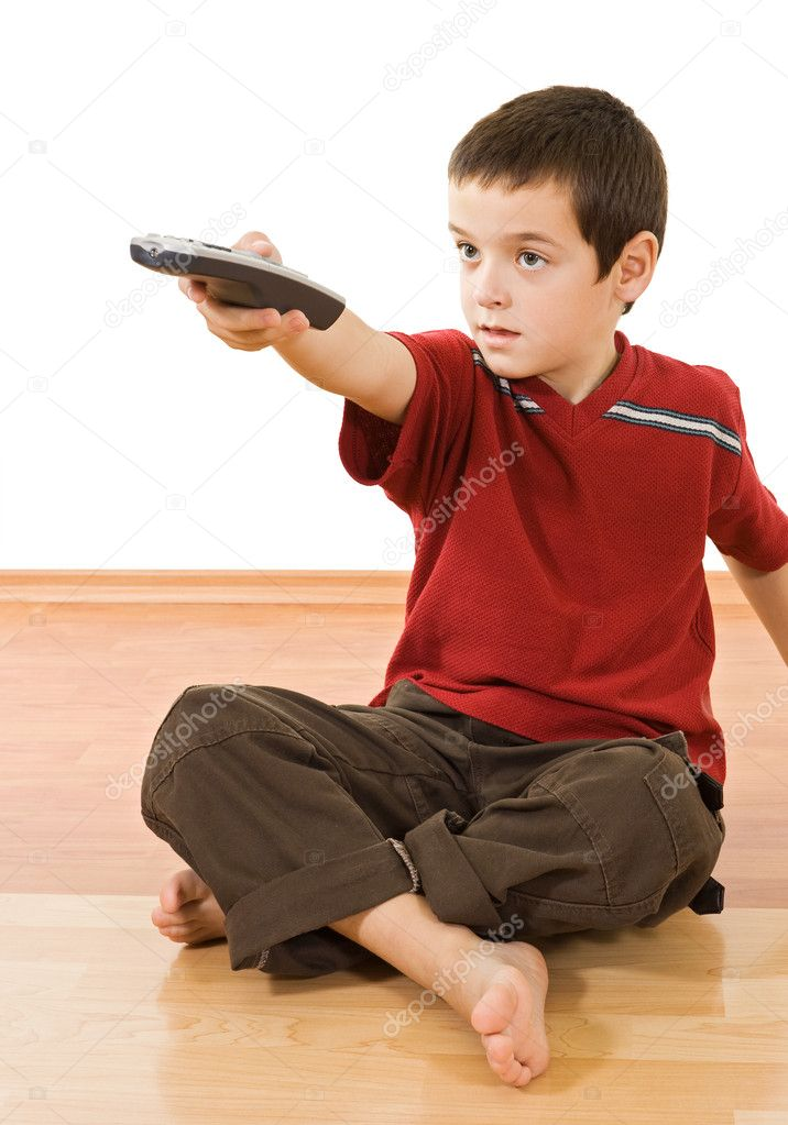 Little boy with a remote control sitting on the floor and watching tv — Stock Photo #10595046