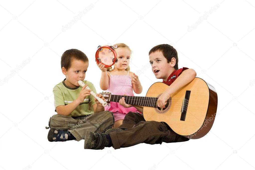Three children sitting on the floor and playing with musical instruments — Stock Photo #10595051