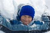 Boy lying in snow — Stockfoto