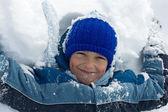 Boy lying in snow — Stock Photo