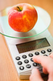 Apple on kitchen scale — Stock Photo