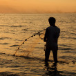 Fisherman at beach with fishing net during sunset — Stock Photo #10502282