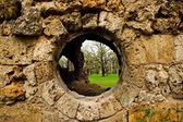 The round window in the old wall. — Stock Photo