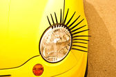 Funny lamp with lashes of yellow small car. — Stock Photo