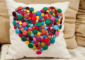 Cushion embellished with colourful buttons — Stock Photo