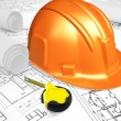 Helmet with ruler placed on blueprint of house - Stock Photo