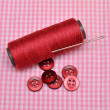 Thread bobbin and buttons on cute checked material — Stock Photo
