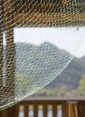 Landscape Through Fishing Net photo taken from table in a restaurant — Stock Photo