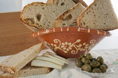 Clay basket with homemade bread and olives — Stock Photo