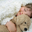 Girl with a white blanket and a soft toy dog — Stock Photo