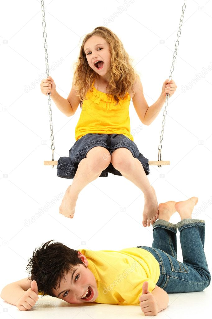 Adorable child couple portrait, girl kicks boy on ground while swinging.  Over white background. — Stock Photo #10553834