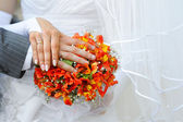 Hands and rings on wedding bouquet — Stockfoto