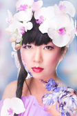 A woman with an orchid flower — Stock Photo