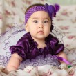 A baby in the purple hat - Stock Photo