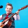 Royalty-Free Stock Photo: A boy with microphone and guitar