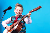 A boy with microphone and guitar — Stock Photo