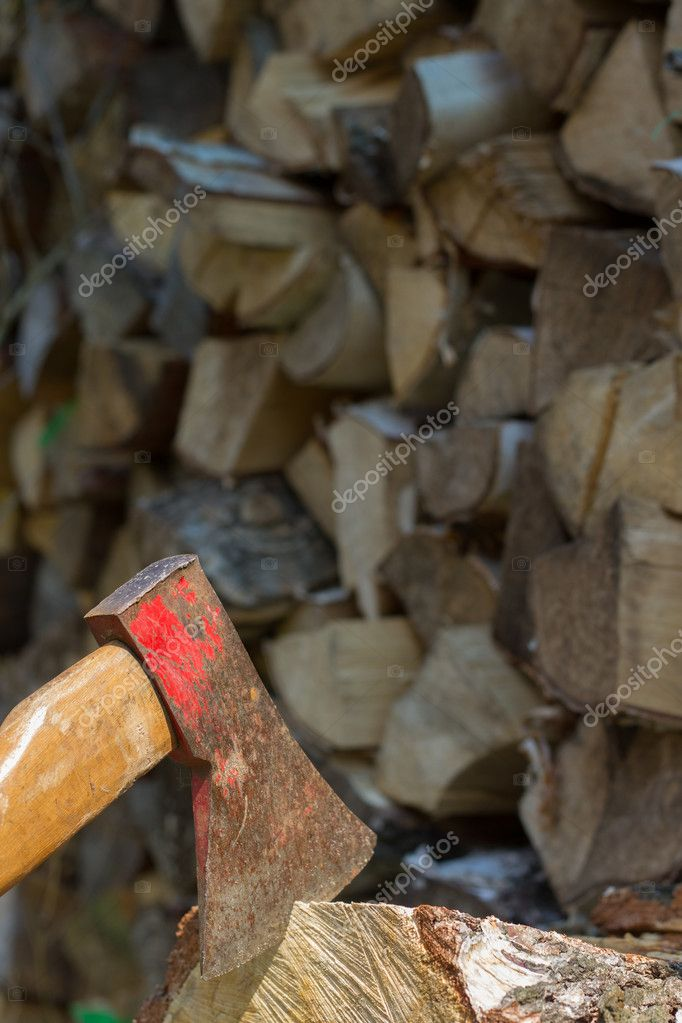 Axe placed in front of a stack of wood — Stock Photo #10695753