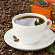 Cup of coffee with beans on wood background - Stock Photo
