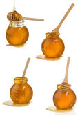 Glass pot full of honey and stick on white — Stock Photo