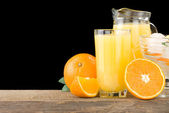 Fresh orange fruits juice and slices isolated on black — Stock Photo
