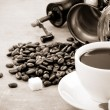 Cup of coffee and grinder with beans — Stock Photo