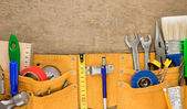 Tools in leathern belt on wood — Stock Photo
