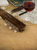 Guitar, glass of wine and note — Stock Photo