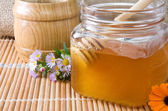 Honey and flowers on wood — Stock Photo