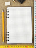 Checked notebook and tepe measure on wood — Stock Photo