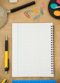 School accessories and checked notebook on wood — Stok fotoğraf