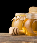 Jar full of honey and stick — Stock Photo