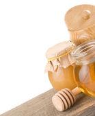 Jar full of honey and stick — Stock Photo