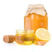 Jar full of honey and lemon on white — Stock Photo